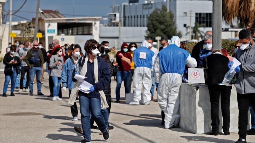 Los israelíes se reúnen en una mesa de votación especialmente erigida para los 5600 votantes en cuarentena, en Haifa, 2 de marzo de 2020. (Foto: AFP)