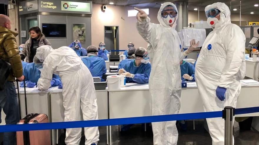 Expertos rusos revisan a los pasajeros que llegan de Italia al aeropuerto internacional Sheremetyevo de Moscú, la capital.