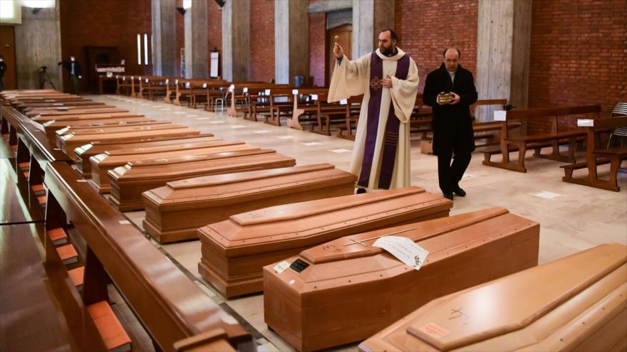 Un sacerdote italiano da bendición a los ataúdes de las víctimas del COVID-19 en la iglesia de San Giuseppe en Seriate, 28 de marzo de 2020. (Foto: AFP)