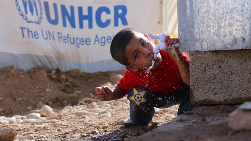 Un refugiado sirio bebe agua de un tanque en un campamento de Qushtapa, en las afueras de la ciudad de Arbil, en el Kurdistán iraquí. (Foto: Reuters)