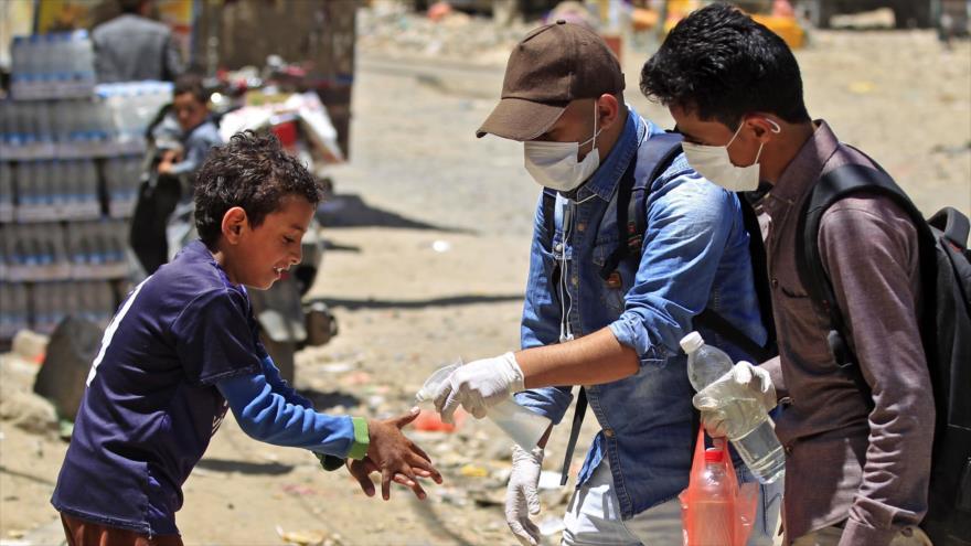 Un voluntario yemení rocía desinfectante en las manos de un niño en Saná, capital, 30 de marzo de 2020, (Foto: AFP)