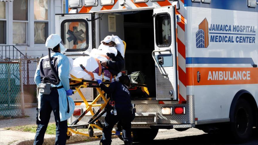 Personal de emergencia introduce a un contagiado por coronavirus en una ambulancia en Nueva York, 24 de marzo de 2020.