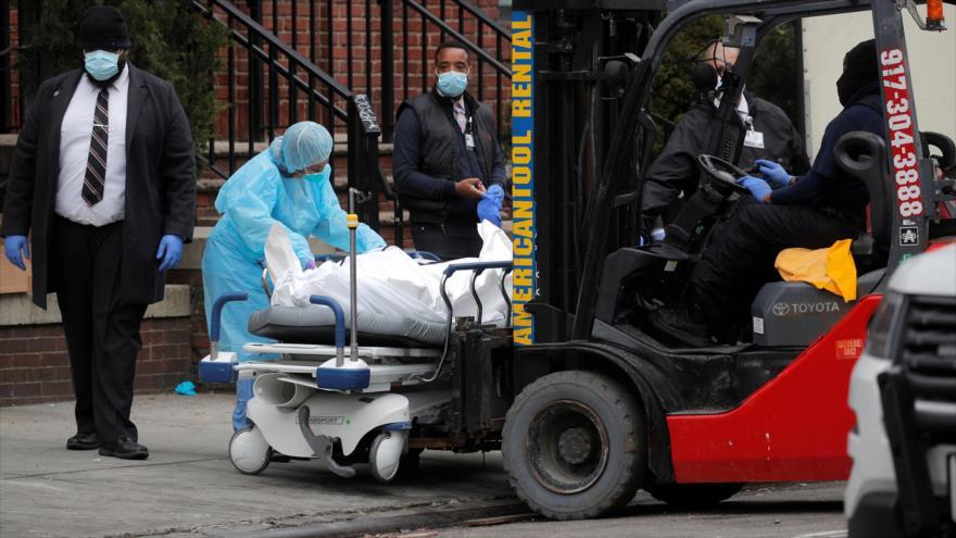 Los trabajadores ponen cadáver de una persona fallecida por el COVID-19 en un remolque, Nueva York, EE.UU., 30 de marzo de 2020. (Foto: Reuters)