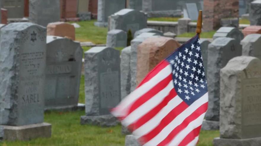 Una bandera nacional de EE.UU. junto a una tumba en un cementerio cualquiera de esta nación norteamericana.