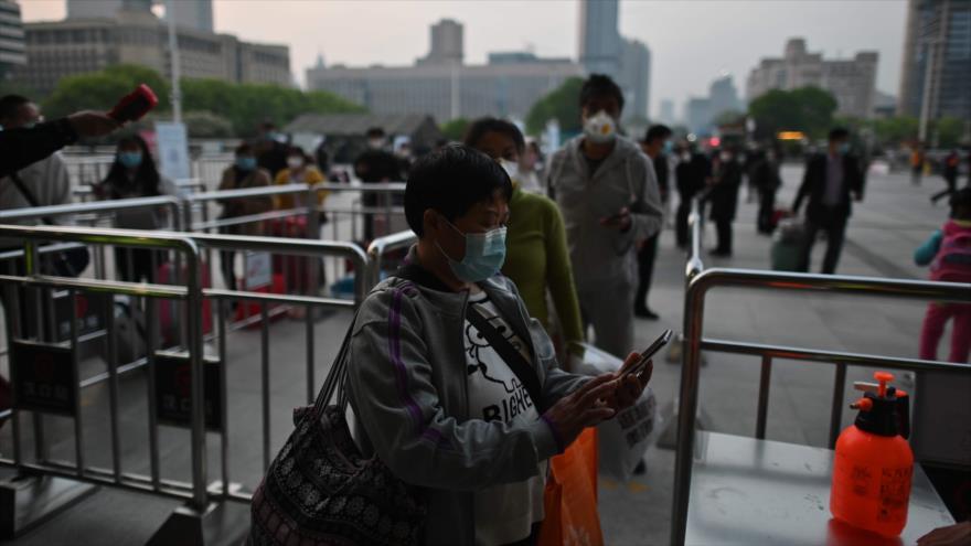 Personas con mascarillas revisan su código de salud de Wuhan frente a la estación de tren de Hankou en Wuhan, 8 de abril de 2020. (Foto: AFP)