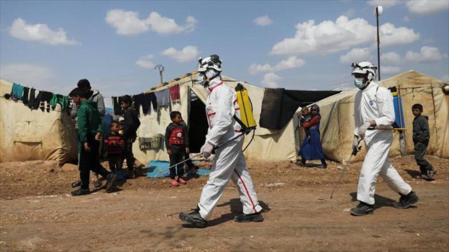 Agentes sanitarios rocían desinfectante en un campo de refugiados sirios para detener propagación del coronavirus, 26 de marzo de 2020. (Foto: Reuters)
