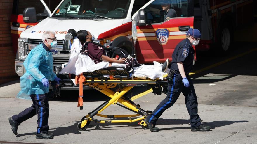 Un equipo del personal sanitario traslada a una paciente afroamericana con síndrome del COVID-19 a un centro hospitalario en EE.UU.