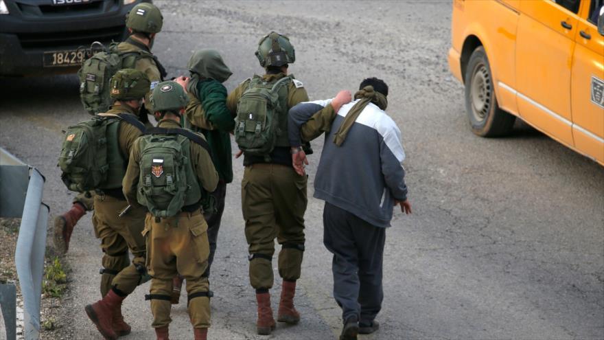 Soldados israelíes detienen a dos palestinos en una aldea cerca de Ramalá, en la Cisjordania ocupada, 17 de febrero de 2020. (Foto: AFP)
