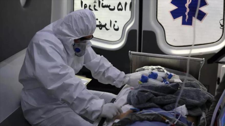 El personal médico iraní ofrece ayuda a un enfermo con COVID-19 en una ambulancia.