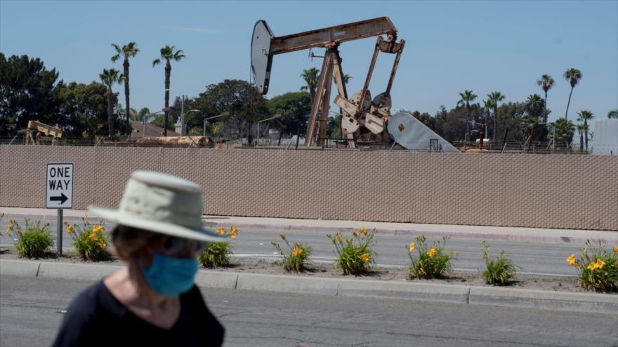 Una peatón con una mascarilla protectora pasa junto a una planta petrolera en Huntington Beach, en California (EE.UU.), 25 de abril de 2020. (Foto: Reuters)