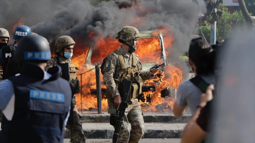 Un soldado del Ejército libanés junto a un auto en llamas durante las protestas en la ciudad norteña de Trípoli, 28 de abril de 2020. (Foto: AFP)