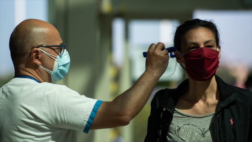 Un trabajador médico (L) escanea la temperatura corporal de una persona el 6 de mayo de 2020 cuando llega al hospital Tor Vergata Covid en Roma. (FOTO: AFP)