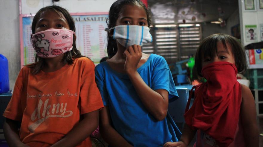 Los niños con máscaras en el edificio de una escuela ubicada en la ciudad de Sorsogon, región de Bicol, sur de Manila, 14 de mayo de 2020. (Foto: AFP)
