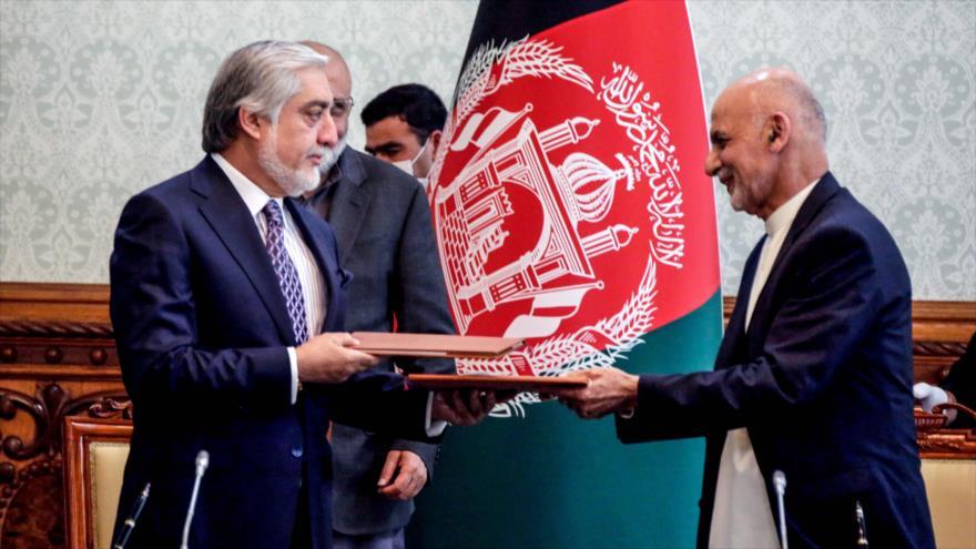 El presidente afgano, Ashraf Qani (dcha.), y su rival, Abdulá Abdulá, intercambian documentos tras firmar un acuerdo en Kabul, 17 de mayo de 2020. (Foto: AFP)