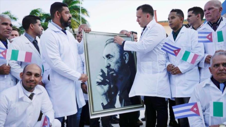 Médicos cubanos sostienen el retrato de Fidel Castro antes de partir al norte de Italia, 21 de marzo de 2020, para tratar pacientes diagnosticados con COVID-19.