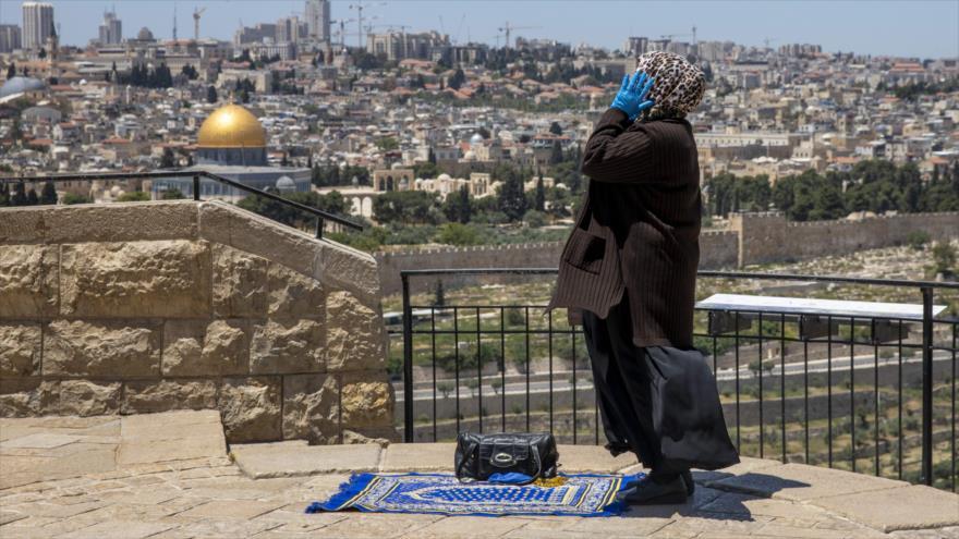 Una fiel musulmana reza en Al-Quds (Jerusalén) a una distancia lejana de la explanada de las Mezquitas de esta santa ciudad.