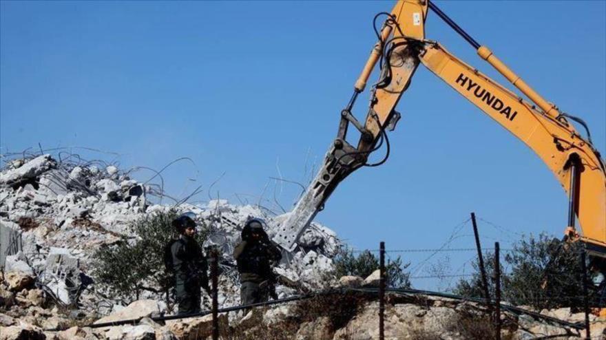 Fuerzas israelíes tratan de mantener alejados a palestinos, cuyas viviendas están siendo demolidas, Cisjordania.