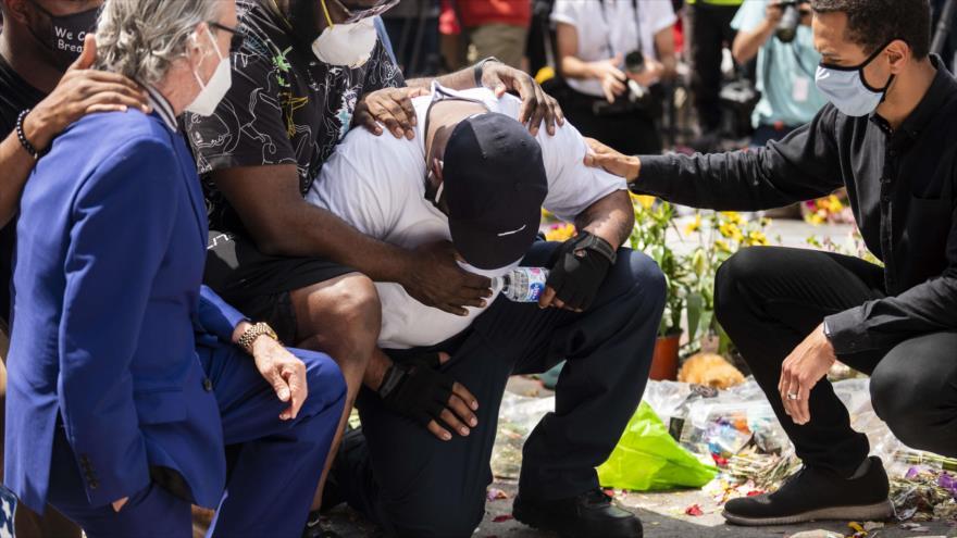 Terrence Floyd (centro) cae de rodillas en el sitio donde su hermano George Floyd fue asesinado por la policía hace una semana, Minneapolis, 1 de junio de 2020. (Foto: AFP)
