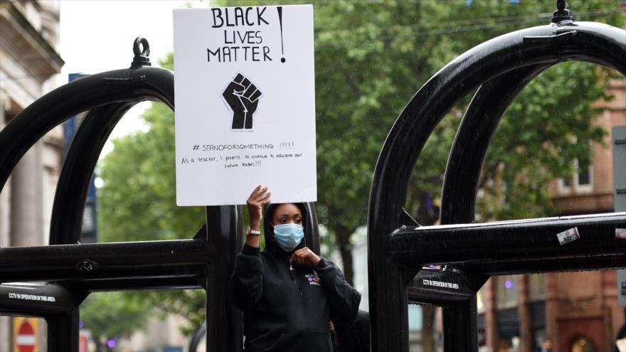 Una manifestante sostiene una pancarta en una protesta contra el asesinato de George Floyd en el centro de Birmingham, 4 de junio de 2020. (Foto: AFP)