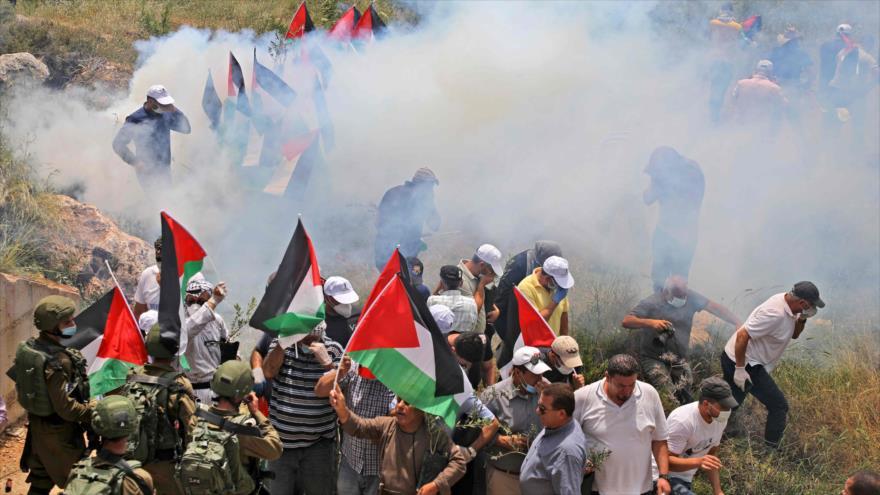 Fuerzas israelíes lanzan gas lacrimógeno contra palestinos que repudian la anexión de Cisjordania, aldea de Al-Sawiya, 15 de mayo de 2020. (Foto: AFP)