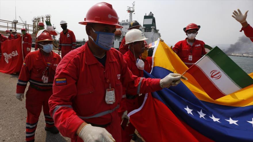 Um petroleiro venezuelano segura uma pequena bandeira iraniana na refinaria El Palito, perto de Puerto Cabello, Venezuela, em 25 de maio.
