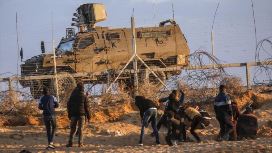 Ciudadanos palestinos lanzan piedras contra un vehículo blindado israelí en la línea divisoria de la Franja de Gaza en los territorios ocupados.