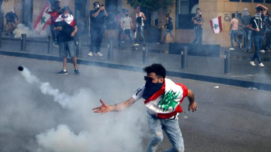 Un manifestante libanés arroja un bote de gas lacrimógeno durante un choque con la Policía antidisturbios, Beirut, 6 de junio de 2020. (Foto: AFP)