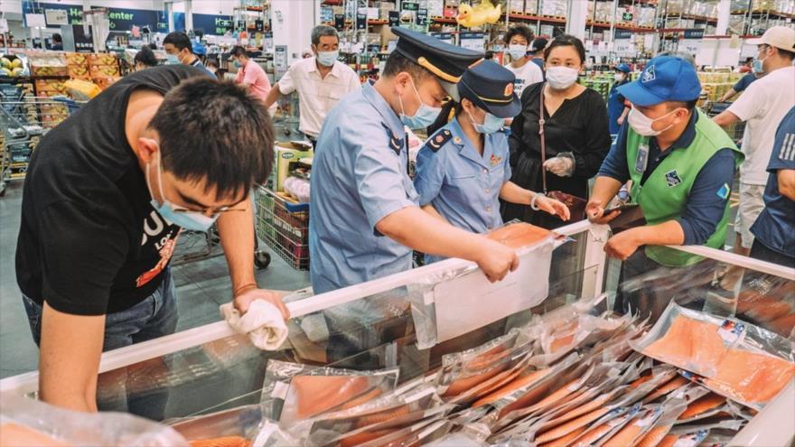 Los empleados de la Administración de Drogas y Alimentos revisan el salmón en una tienda en Pekín, la capital china, 13 de junio de 2020.