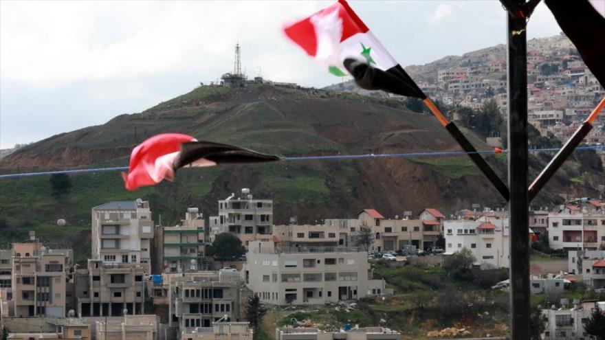 Banderas sirias en la localidad de Ain al-Tineh, frente a la ciudad drusa de Majd al-Shams en el Golán ocupado, 26 de marzo de 2019. (Foto: AFP)