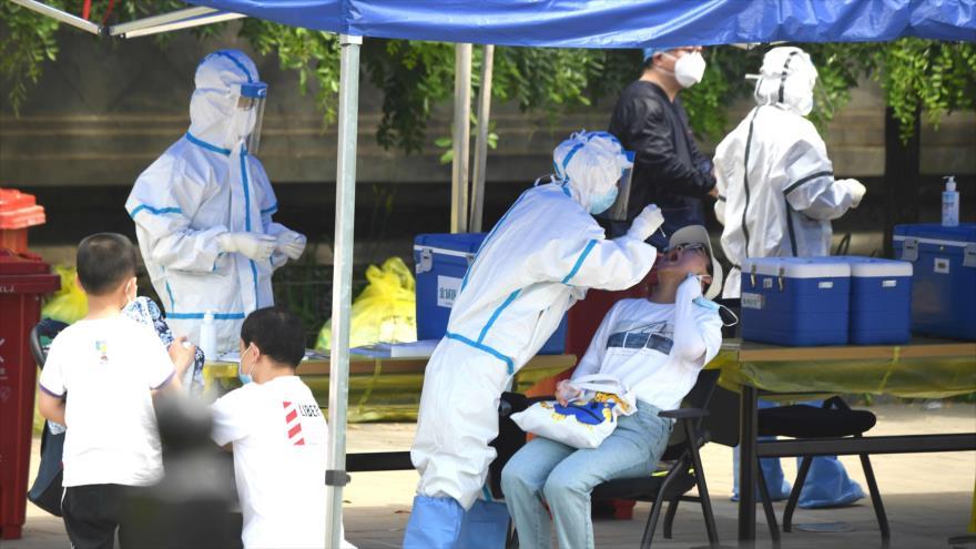 Trabajadores de la salud chinos toman pruebas de hisopo en Pekín, la capital, 16 de junio de 2020. (Foto: AFP)