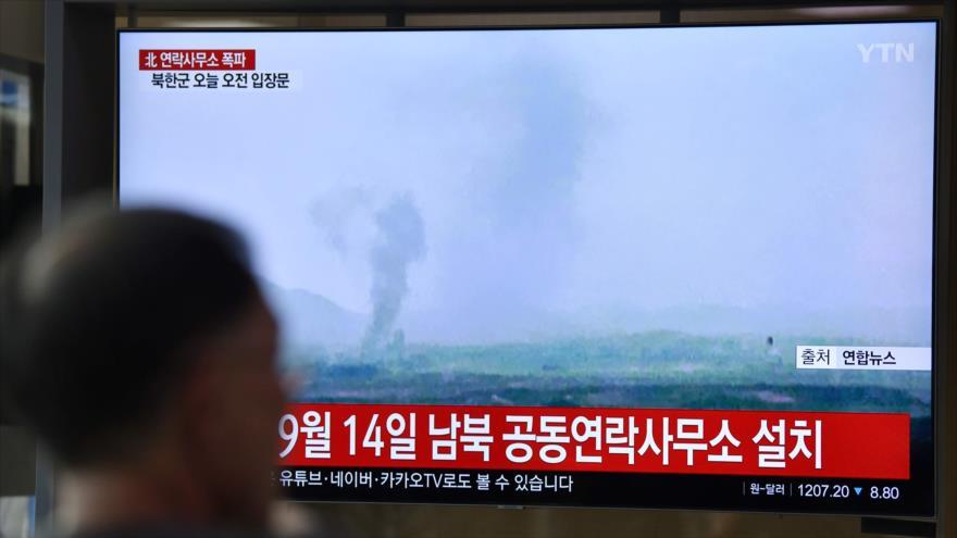 Un hombre mira una pantalla de televisión que muestra la explosión de una oficina de enlace intercoreana en el Complejo Industrial Kaesong de Corea del Norte, 16 de junio de 2020. (Foto: AFP)