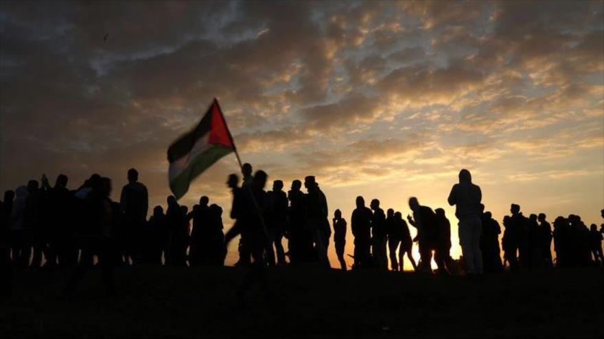 Palestinos enarbolan su bandera nacional en una protesta en la ocupada Cisjordania.