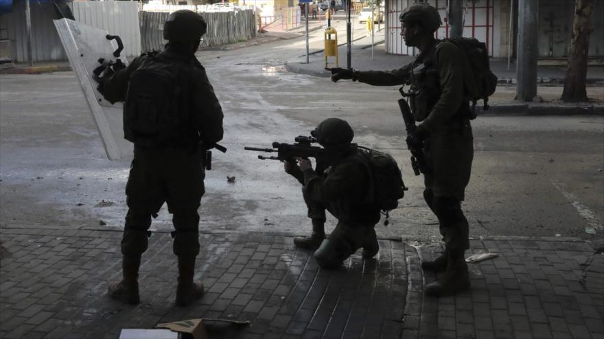 Soldados israelíes apuntan contra manifestantes palestinos en una protesta en Al-Jalil (Hebrón), Cisjordania ocupada, 31 de enero de 2020. (Foto: AFP)