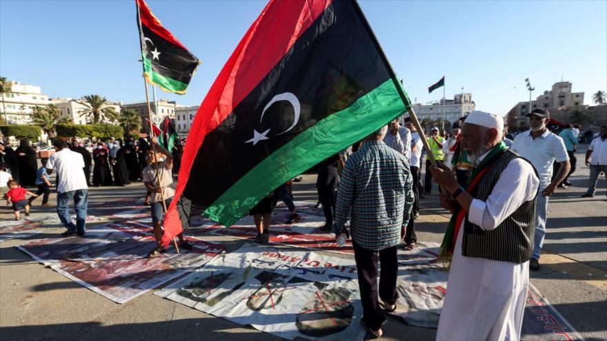 Un hombre ondea una bandera nacional de Libia en el centro de la capital libia, Trípoli, en manos del Gobierno de Acuerdo Nacional (GNA), 21 de junio de 2020. (Foto: AFP)
