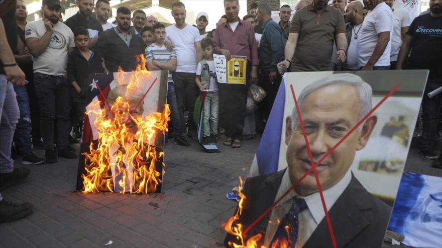 Palestinos queman fotos del presidente de EE.UU., Donald Trump, y del premier israelí, Benjamín Netanyahu, Cisjordania, 30 de mayo de 2020. (Foto: AFP)
