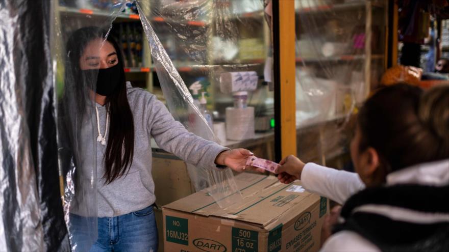 Una vendedora recibe a una cliente por detrás de una cortina de plástico para evitar la propagación de coronavirus, México, 22 de junio. (Foto: AFP)