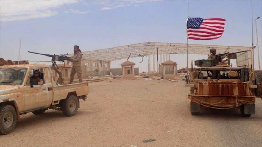 Combatientes de un grupo armado ilegal, apoyado por EE.UU., al lado de un vehículo blindado estadounidense en Siria, 23 de mayo de 2019. (Foto: AP)