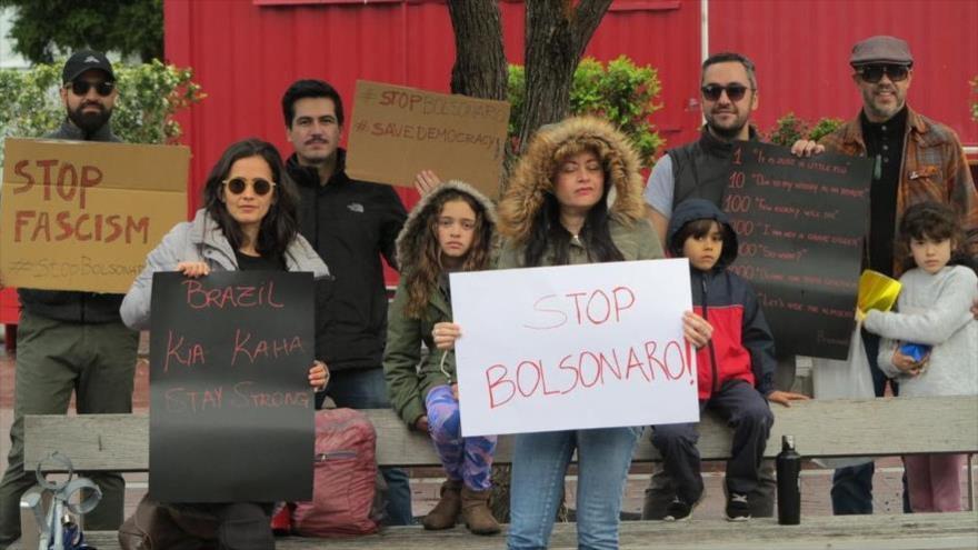 """Unos manifestantes brasileños se manifiestan contra el presidente de Brasil con unas pancartas que dicen """"Stop Bolsonaro""""."""