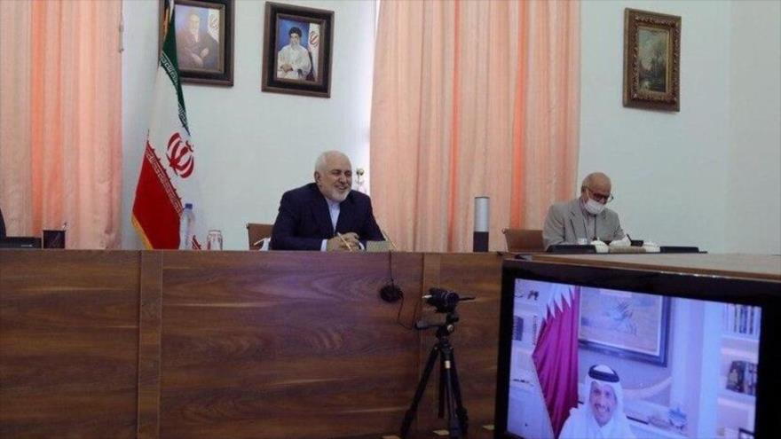 El canciller iraní, Yavad Zarif (1º a la izq.), mantiene una reunión virtual con su par catarí, Muhamed bin Abdulrahman Al Thani, 29 de junio de 2020.