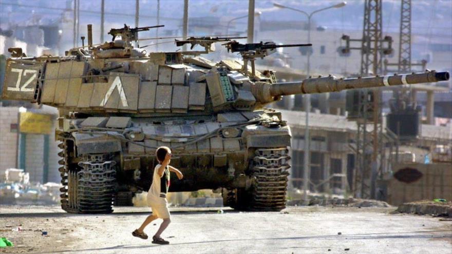 Un niño palestino lanza piedras contra un tanque israelí en la Cisjordania ocupada.