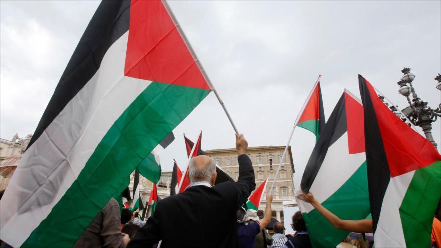 La gente ondea las banderas de Palestina cuando el papa Francisco celebra una oración en el Vaticano.