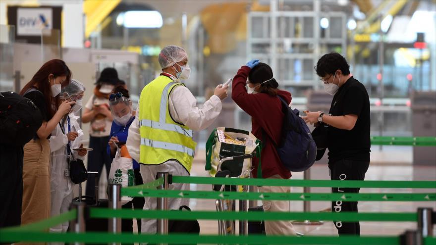 Empleado sanitario verifica temperatura de pasajeros de un vuelo con destino a Pekín, aeropuerto de Barajas, Madrid, 20 de junio de 2020. (Foto: AFP)