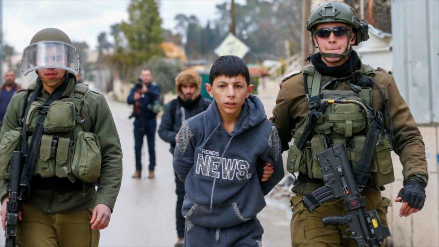 Soldados israelíes detienen a un palestino de 13 años en la ocupada Cisjordania, 11 de febrero de 2020. (Foto: AFP)