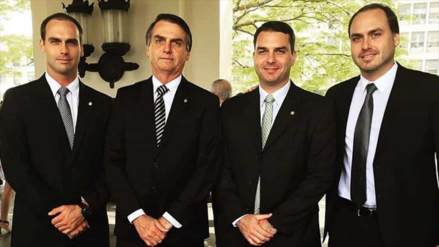 El presidente de Brasil, Jair Bolsonaro (2º izq.), con sus hijos, Eduardo, Flávio y Carlos.