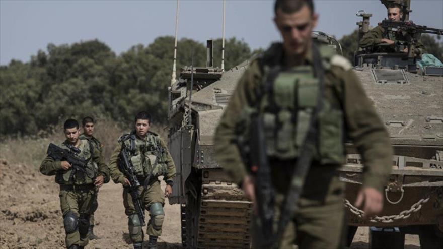 Un grupo de soldados israelíes montan guardia junto a un tanque del ejército del régimen de Israel en la Cisjordania ocupada.