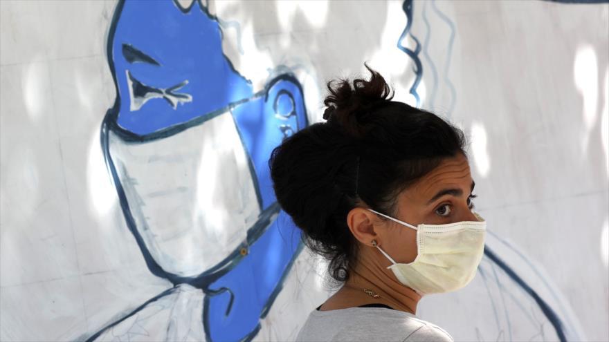 Una mujer frente a un mural pintado en honor del trabajo de los sanitarios en lucha contra COVID-19, California, 22 de junio de 2020. (Foto: AFP)
