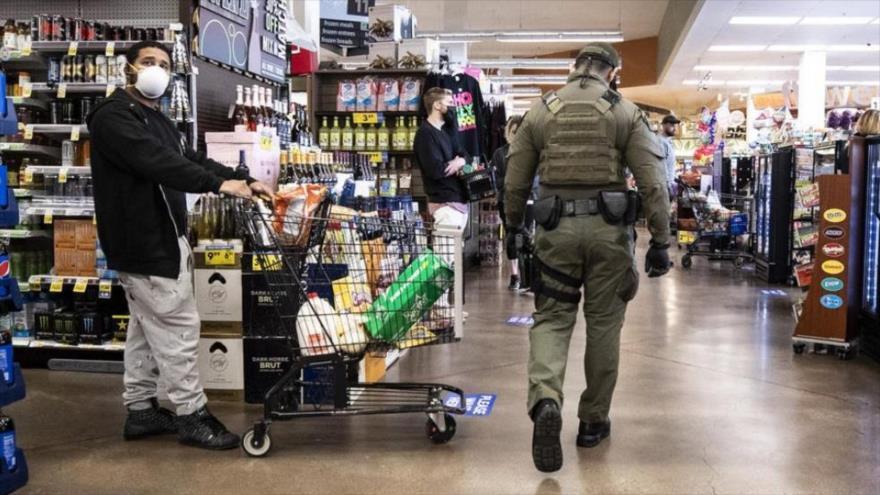 Un alguacil patrulla un supermercado en Los Ángeles, para que se mantenga el distanciamiento social. (Foto: EFE)
