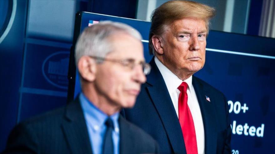 El presidente de EE.UU., Donald Trump, mira seriamente al Dr. Anthony Fauci, principal asesor en epidemiología de la Casa Blanca, en una sesión sobre el coronavirus.