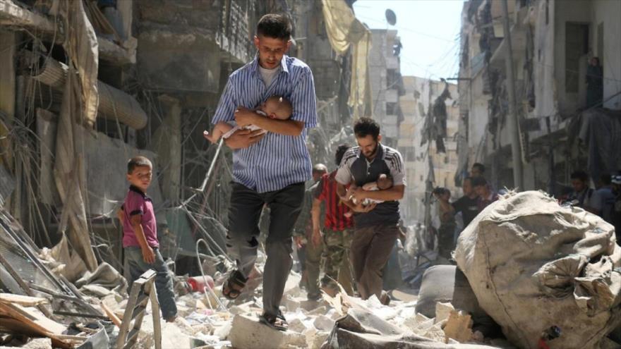 Hombres sirios llevan a bebés, rescatados de los escombros tras un ataque aéreo contra Alepo, 11 de septiembre de 2016. (Foto: Reuters)