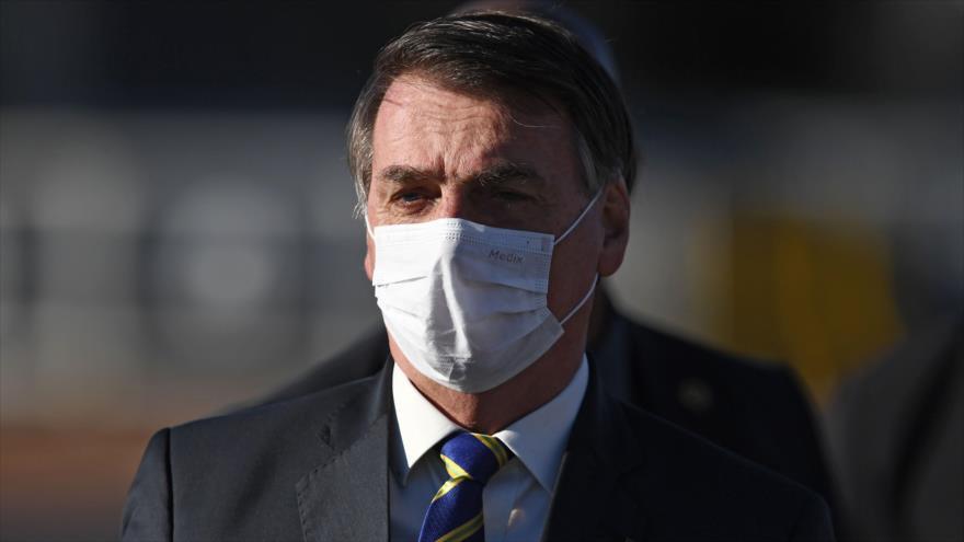 El presidente brasileño, Jair Bolsonaro, usa una mascarilla antes de una reunión ministerial en Brasilia, Brasil, 12 de mayo de 2020. (Foto: AFP)